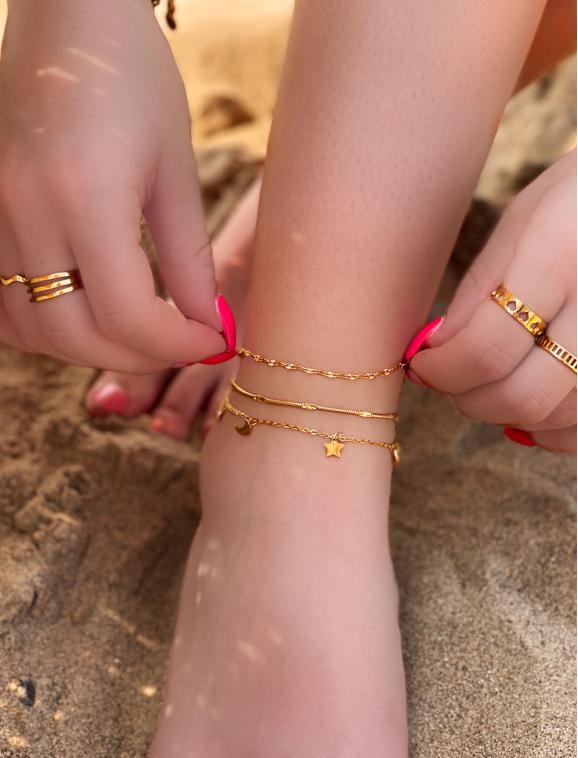 Mooie enkelbandjes om de enkel van het meisje met trendy ringen