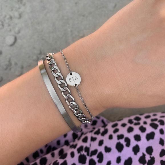 Zilveren armbandjes bij elkaar gecombineerd met witte trui