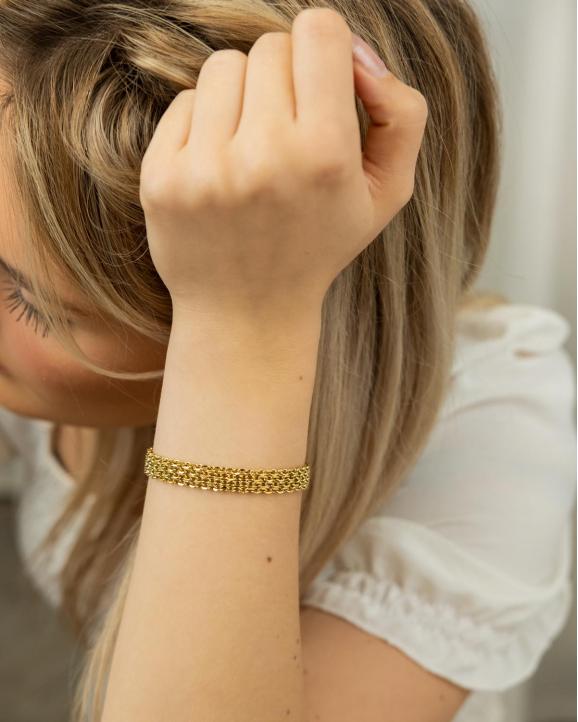Het model draagt de nieuwe platte mesh armband in het goudkleurig