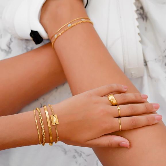 Drie gouden armbanden met elkaar gemixt om pols