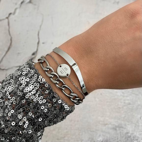Pols met zilveren initial armband en open bangle