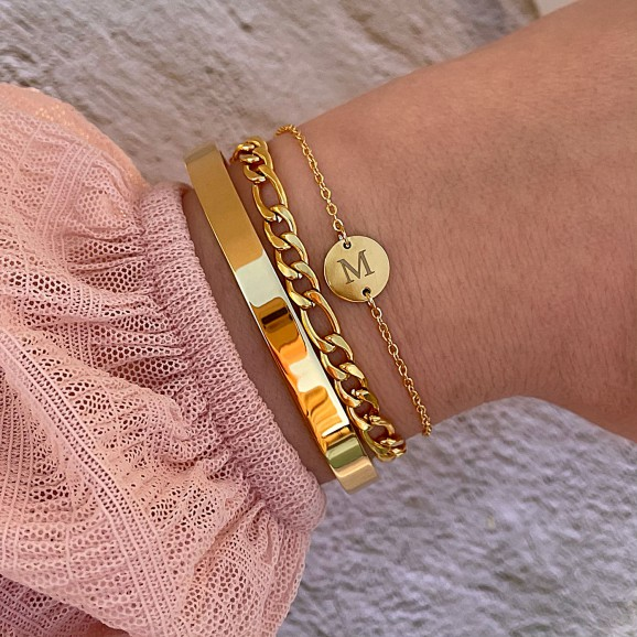 Vrouw draagt mix van mooie goud kleurige armbanden