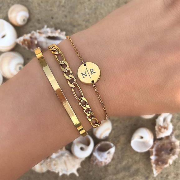 Gouden armbandjes om de pols op het strand
