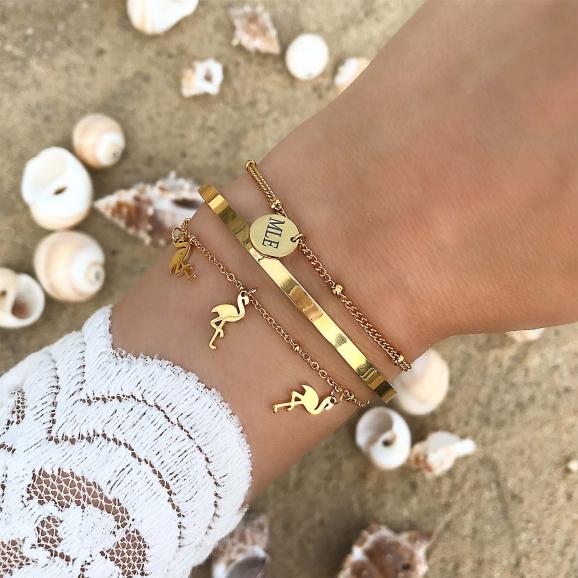 Gouden trendy armbanden om de pols op het strand met schelpen