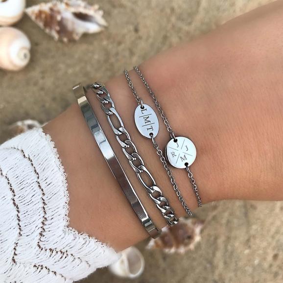 Zilveren schakelarmband om de pols op het strand