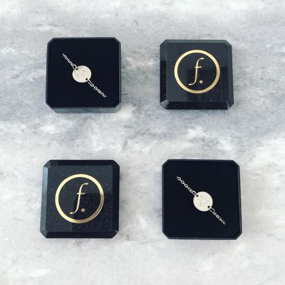 Twee zilveren armbanden met letters