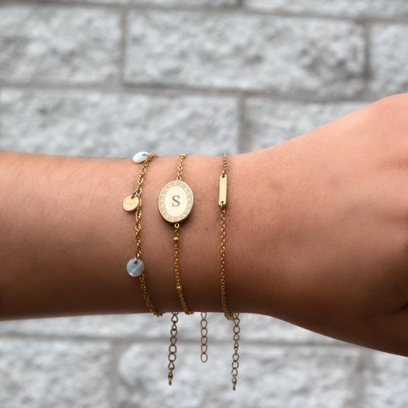Vrouw draagt initial armband goud samen met schelpjes armband