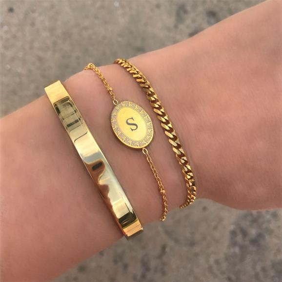 Gouden initial armband om de pols in combinatie met andere gouden