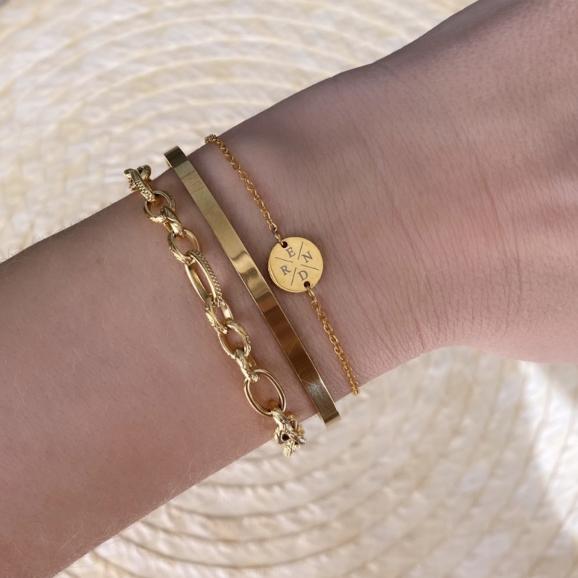 Vrouw draag gouden armcandy om pols met bangle