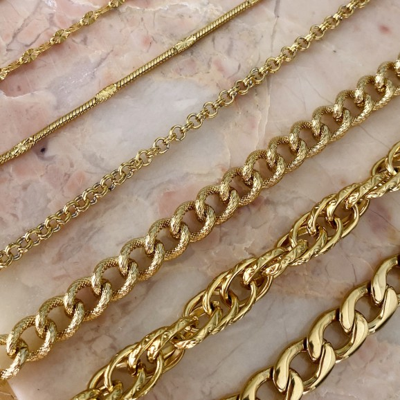 Gouden schakelarmband op een marmer plaatje