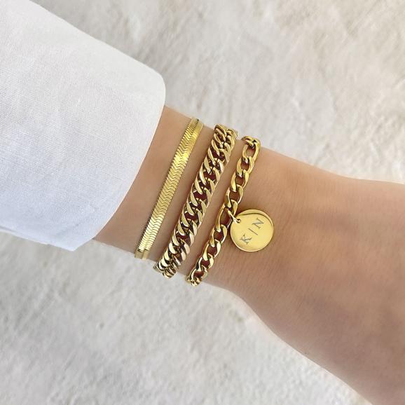 Mix van gouden armbanden met chains en gravering om pols