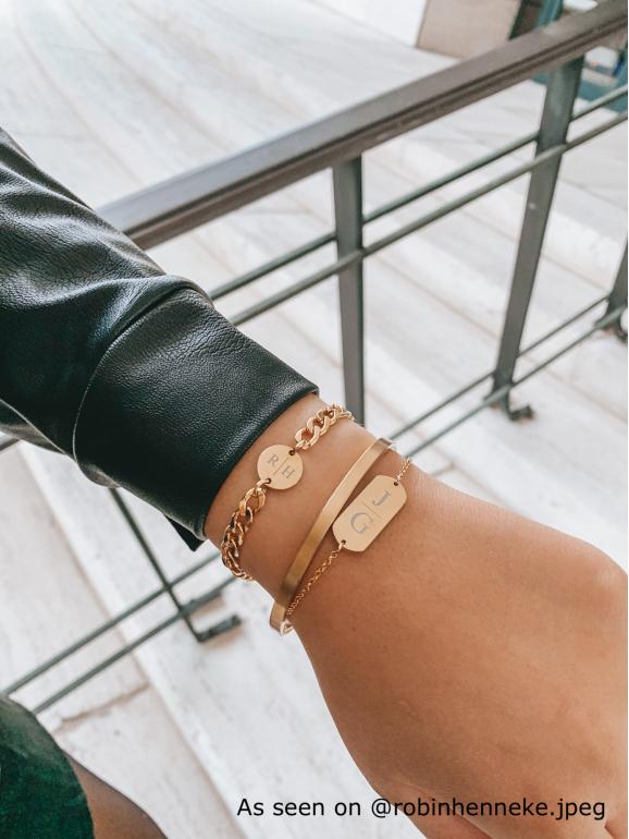 Drie goudkleurige armbandjes om pols