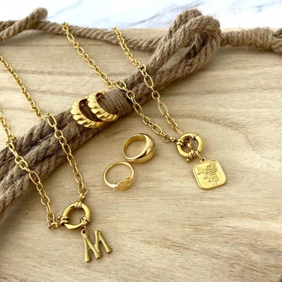 Mooie goudkleurige sieraden mix op een houten achtergrond