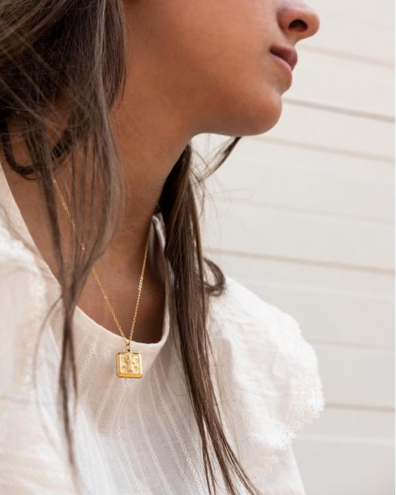 De vintage ketting met hanger in het goud kleurig om de hals