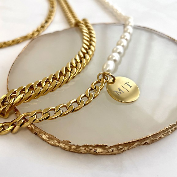 Gouden schakelarmbanden met parels en gravering op plateau