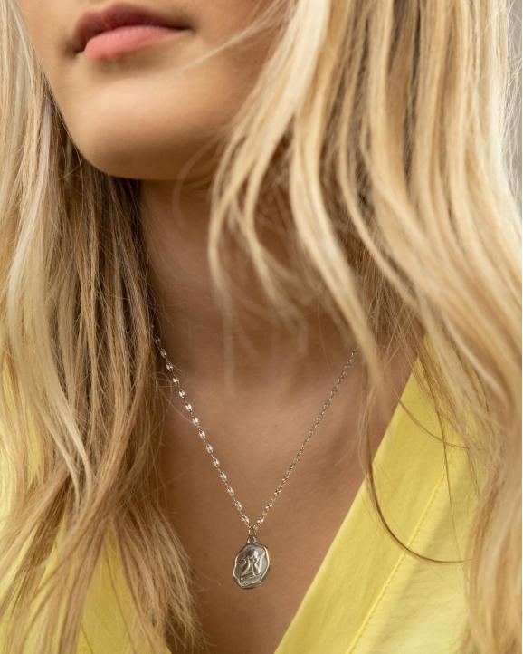 Model draagt een zilveren ketting met een vintage bedeltje engel