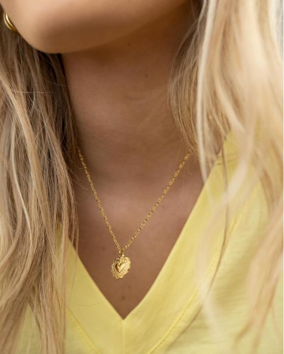 Trendy goudkleurige ketting met een hartjes bedel om de hals bij het model