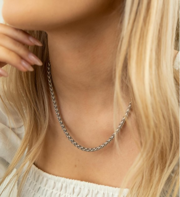 Het model draagt de zilverkleurige ketting met gevlochten chains