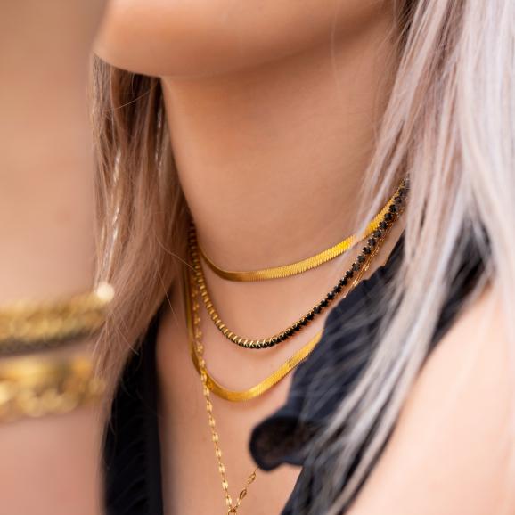 Tennis ketting om de hals van het model in het zwart met goud