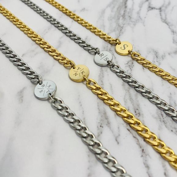 Gouden en zilver initial kettingen op marmeren ondergrond