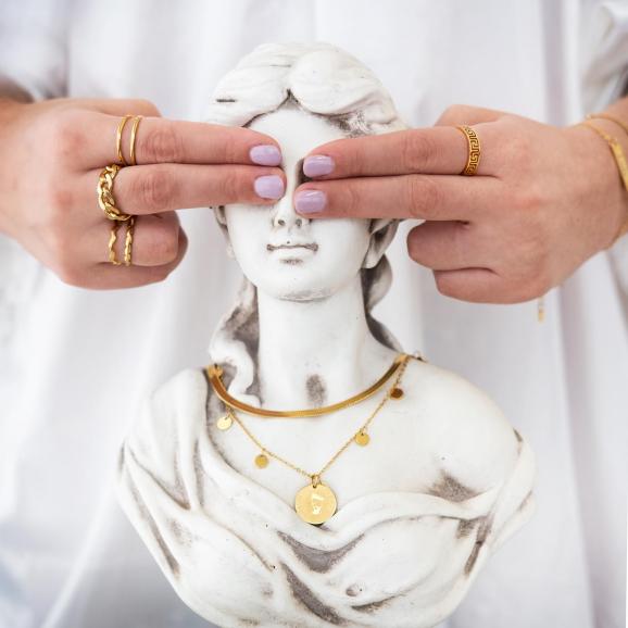 Het model draagt de mooie chain ring in het goudkleurig