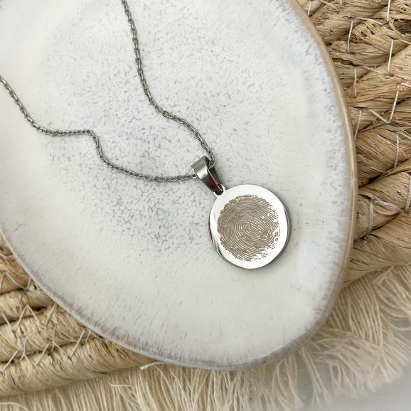 Zilveren vingerafdruk ketting op stenen ondergrond