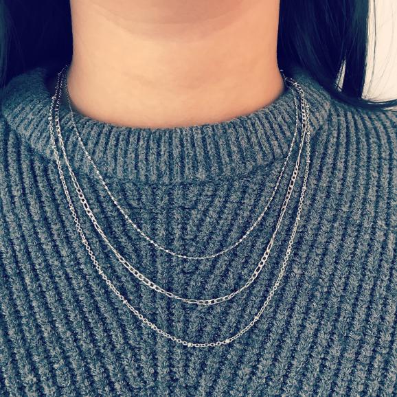 Vrouw draagt verschillende minimalistische schakel kettingen van FINASTE