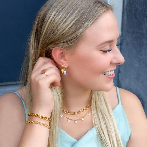 vrouw draagt gouden sieraden om de hals met een graverrbare look