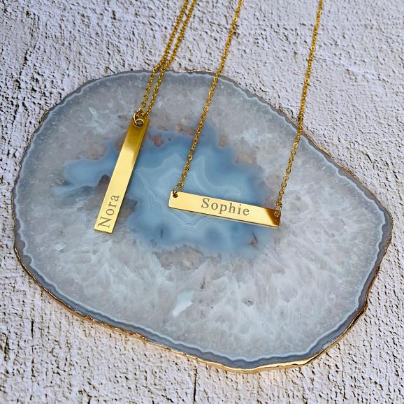 Gouden bar sieraden met naam op stenen ondergrond