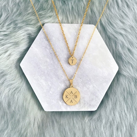 Gouden kettingen met initialen op marmeren plaatje