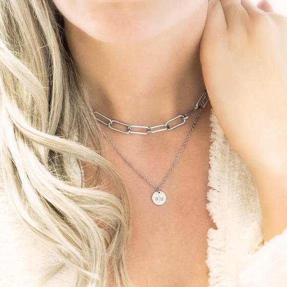 Vrouw draagt een zilveren schakelketting om de hals voor een complete look