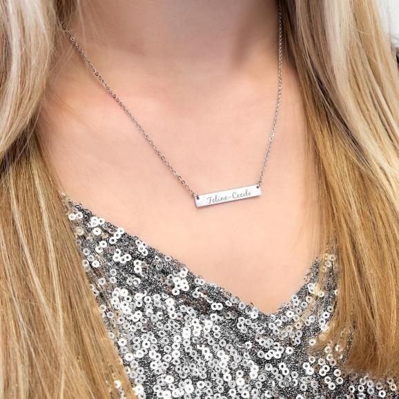 Vrouw draagt zilveren ketting met gravering om de hals
