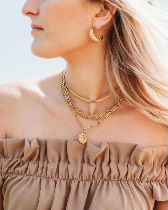 Vrouw draagt gouden croissant oorringen