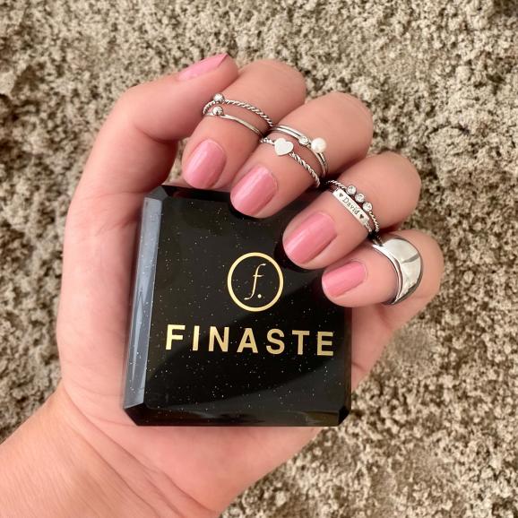 Zilverkleurige ringen in de hand met roze nagellak