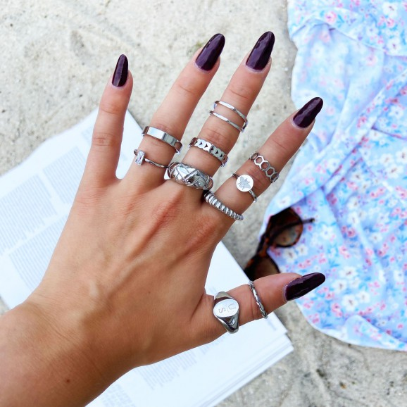 Het model draagt de zilverkleurige ringen om haar hand