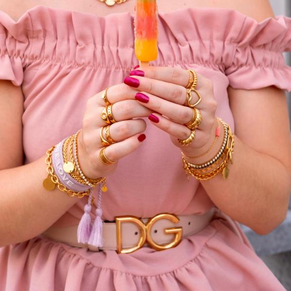 goudkleurige sieraden mix om handen van model