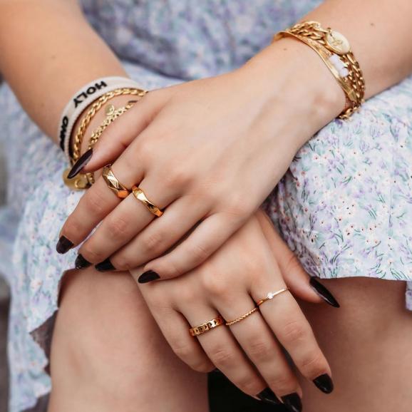 Model draagt gouden ringen om handen