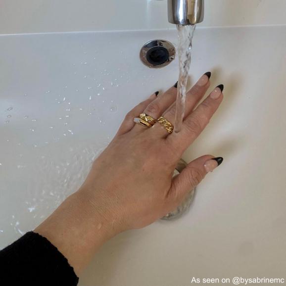 Influencer draagt drie ringen en wast handen
