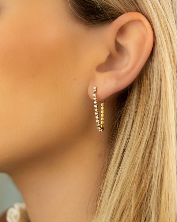Vrouw draagt tennis earrings met kettinkje