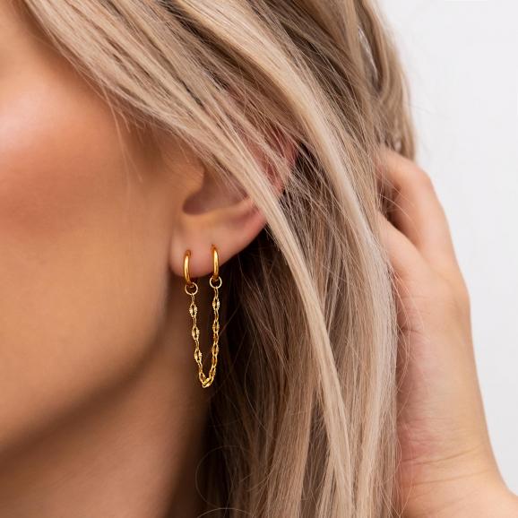 Mooie gouden double hoop oorbellen in het goud in het oor