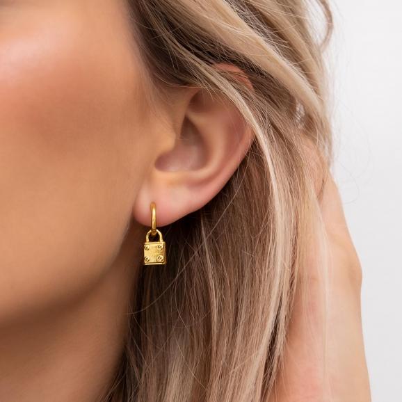Slotje oorbellen in het oor van het model in goud