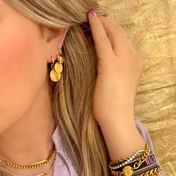 Trendy coin oorbellen goud kleurig in het oor van het model