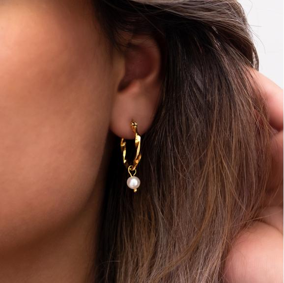 Goud kleurige oorringen in oor