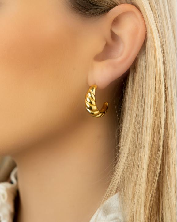 Vrouw draagt gouden croissant oorring in oor