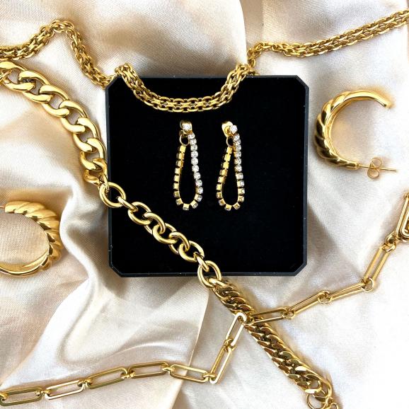 Goudkleurige sieraden op een satijnen doek die je kan combineren voor een mooie look