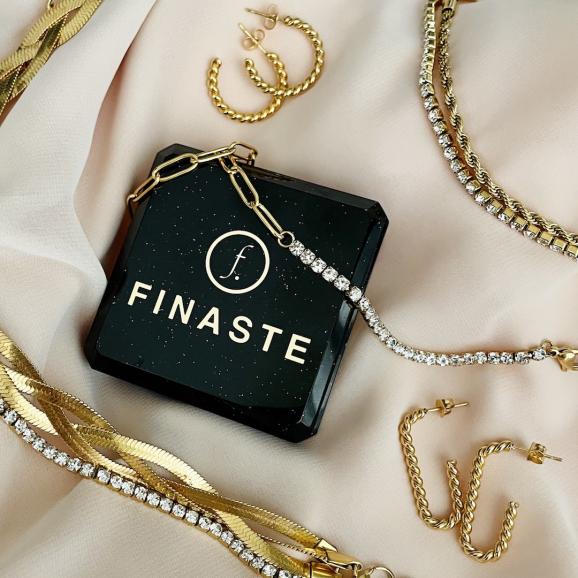 Trendy sieraden op een satijnen doek in het goud