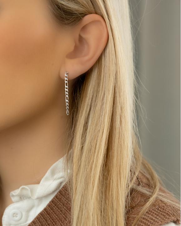 Trendy zilver kleurige oorbellen in het oor van het model met kettinkje