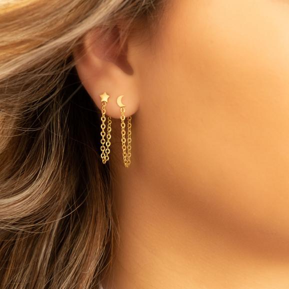 Mooie gouden ketting oorbellen in het oor van het model