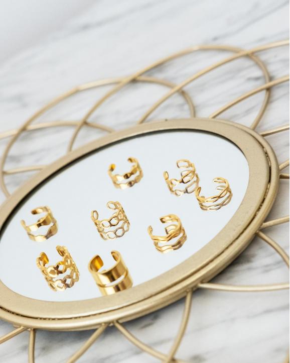 Gouden ear cuffs op een spiegel