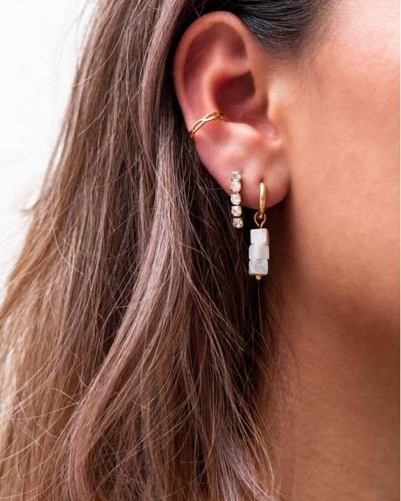 Gouden oorbellen in oor van model